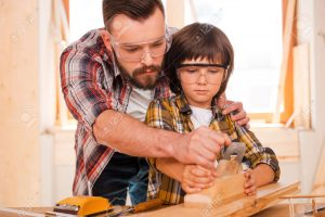 ۴۰۵۶۷۶۳۲-success-is-a-learnable-skill-concentrated-young-male-carpenter-teaching-his-son-to-work-with-wood-in-stock-photo